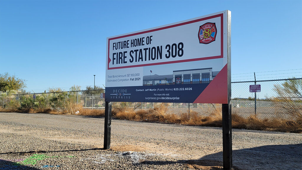 A sign for the future home of fire station 308 in front of a fenced off dirt lot.