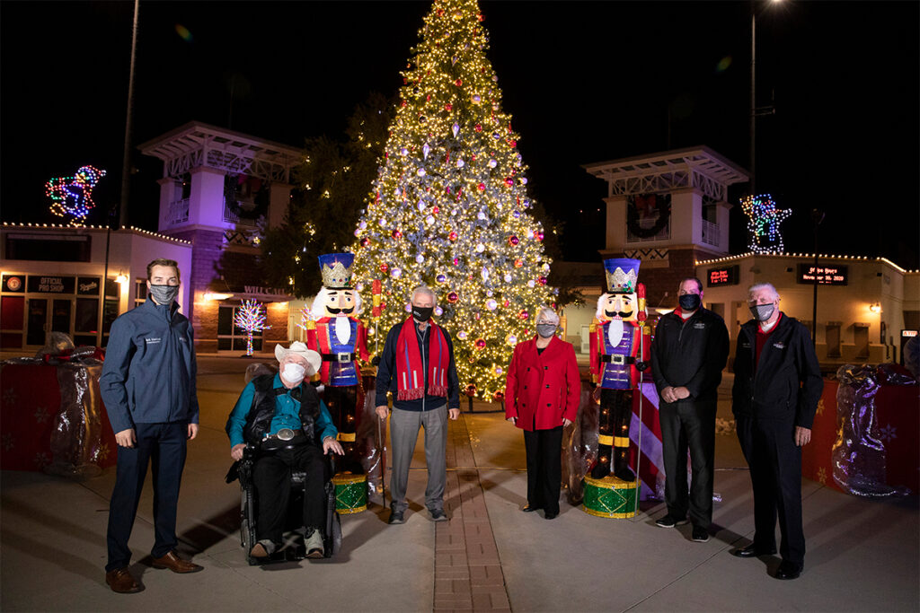 Surprise City Council standing in front of the lit Christmas tree at Surprise Stadium.