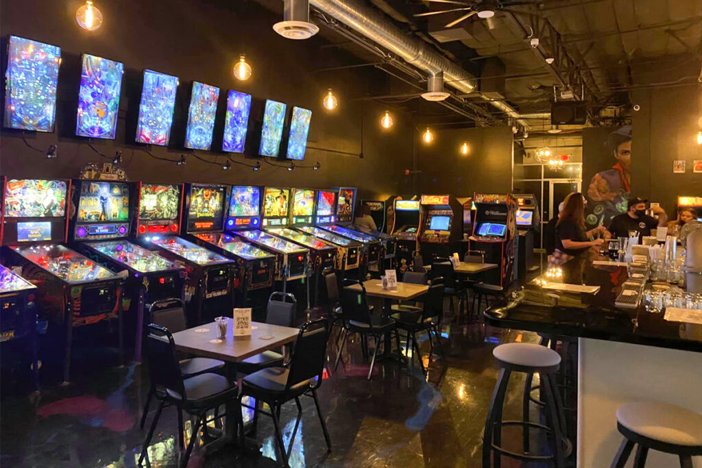 A row of pinball machines line the wall and dining table are centered in the room at Player 1 Arcade.