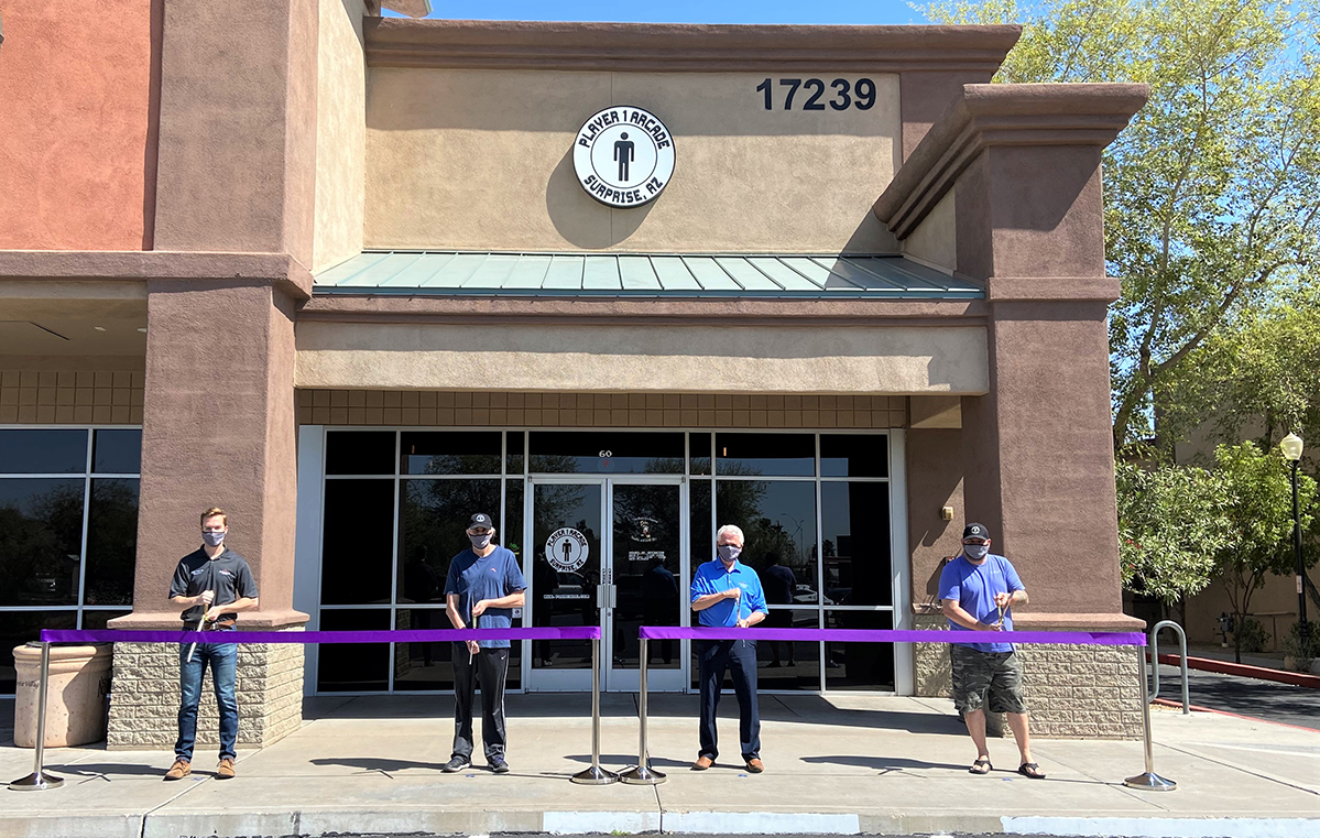 Mayor Hall, Councilmember Hastings, and owners of Player 1 Arcade perform a grand opening ribbon cutting outside of the new business.