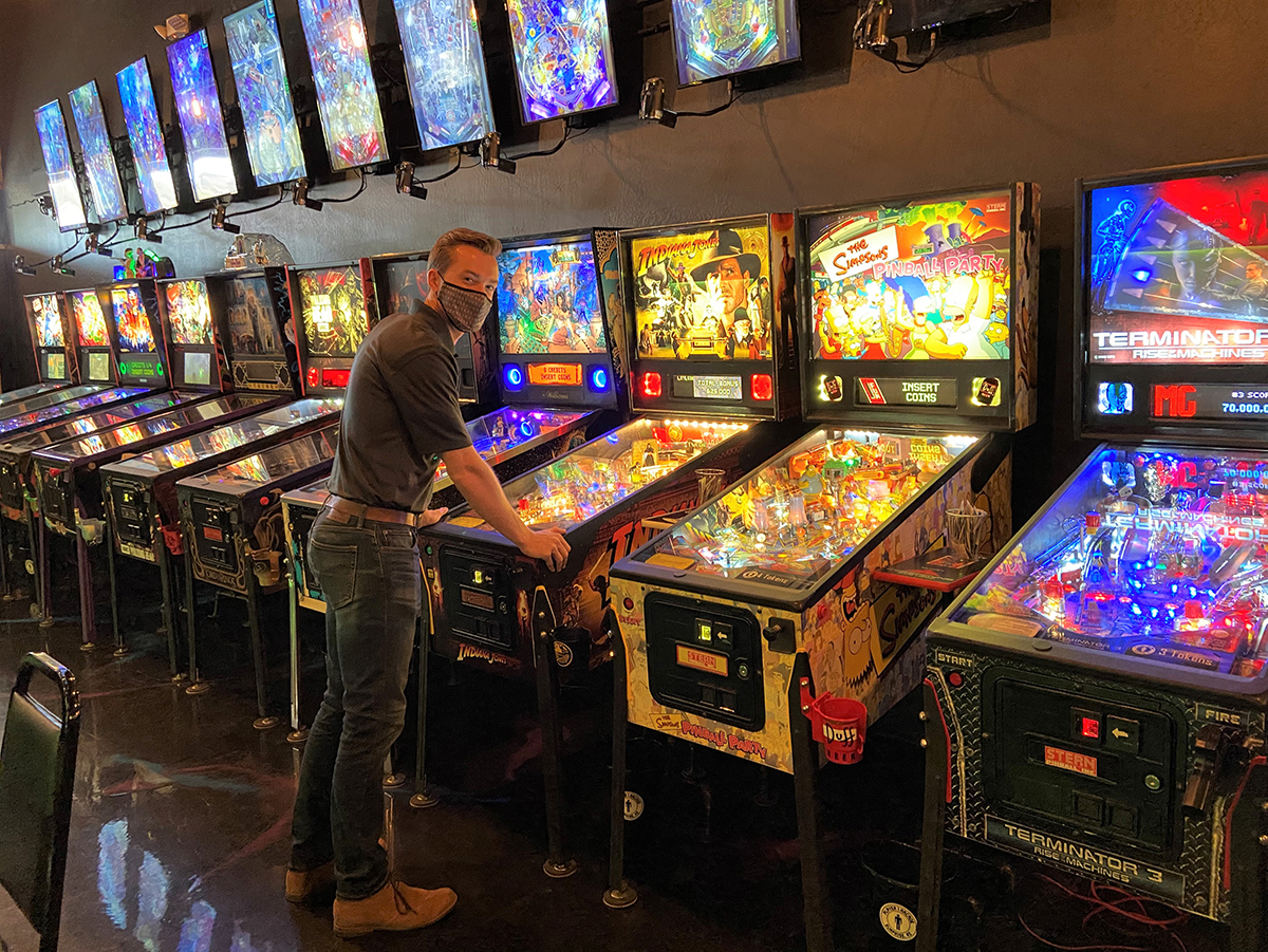 Councilmember Hastings play a game of pinball at Player 1 Arcade.