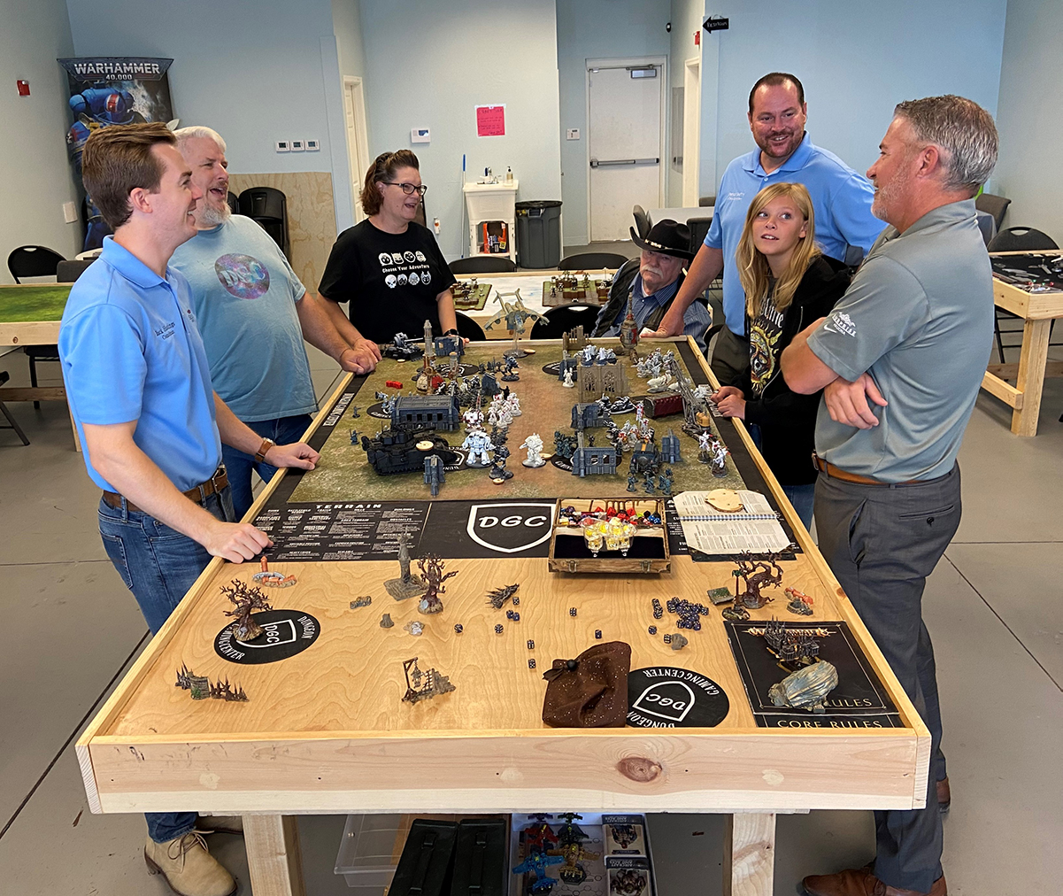 Councilmember Hastings, Councilmember Judd, Vice Mayor Duffy, and Councilmember Winters stand around a Dungeon Gaming Center table.