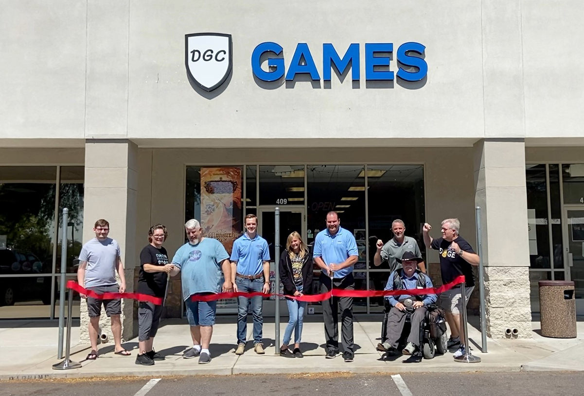 Surprise City Council and Dungeon Gaming Center owners cut a red ribbon in front of the game store.