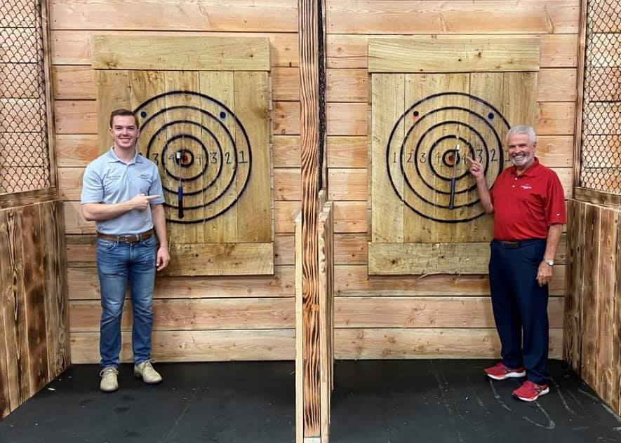 Councilmember Hastings and Mayor Hall point to their axes which are stuck in the bullseye of their targets.