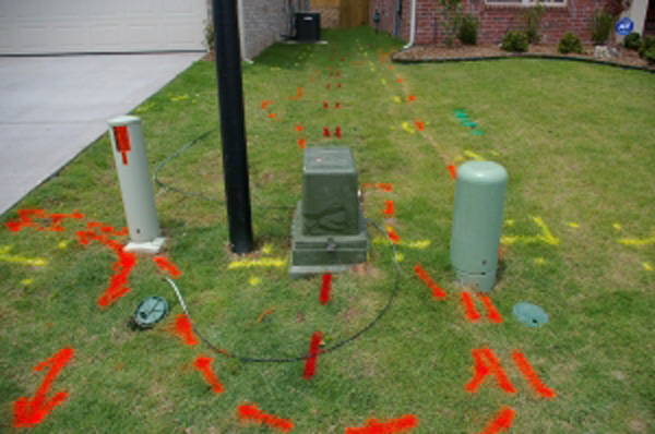 A front yard is marked with red, yellow and orange utility markings.