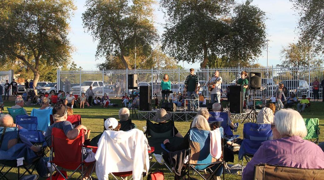 Residents seated in lawn chair watch a music performance at Surprise Sunday in the Park.